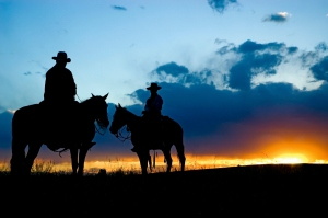 Cowboys, in silhouette, against a dawn sky in Montana